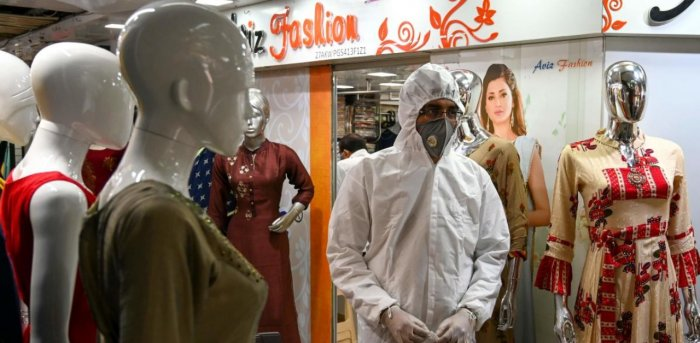 A health worker wearing protective gear waits to collect swab samples from people during a medical screening for the Covid-19 coronavirus at a garment wholesale market in Mumbai on November 20, 2020. Credit: AFP Photo