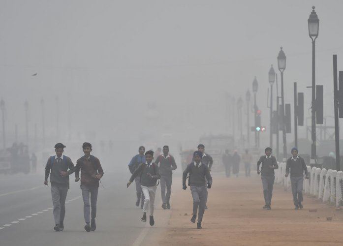 Students run on a cold and wintry morning at Rajpath in New Delhi. Credit: PTI