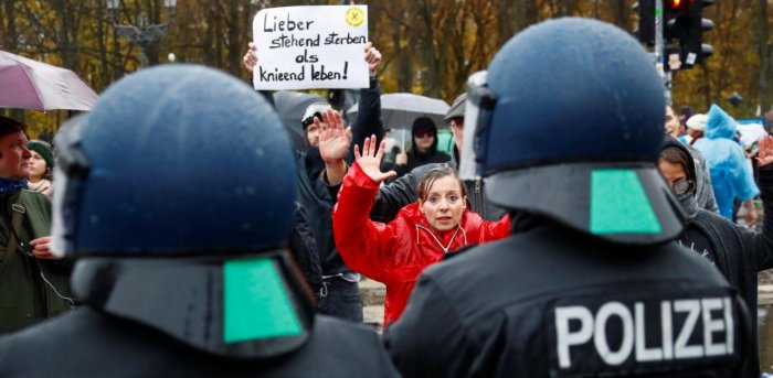 A demonstrator puts her hands up during a protest against the government's coronavirus disease restrictions next to the Brandenburger Gate in Berlin, November, 18, 2020. Credit: Reuters Photo