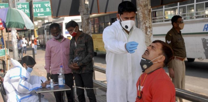 A health worker conducts Covid-19 testing at a bus stop as coronavirus cases surge, in Noida. Credit: PTI Photo