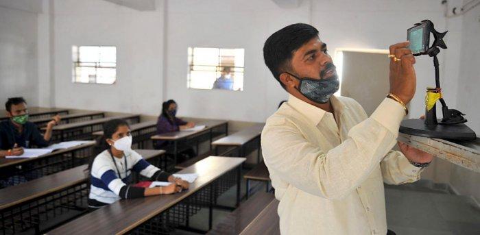 A lecturer adjust the camera to facilitate online learning at Seshadripuram Degree College, Bengaluru, on November 17. Credit: DH photo/Pushkar V.
