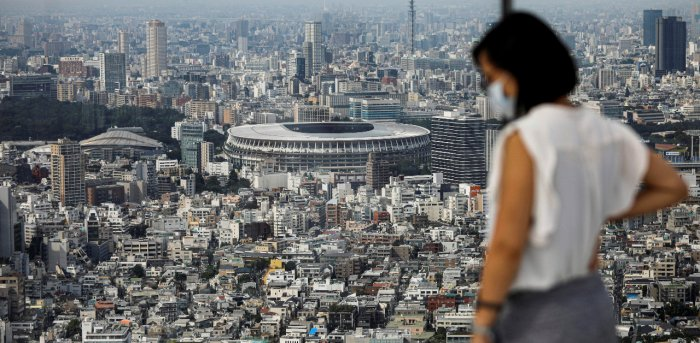 The National Stadium, the main stadium of Tokyo 2020 Olympics and Paralympics, is seen past a visitor wearing a protective face mask amid the coronavirus disease. Credit: Reuters Photo