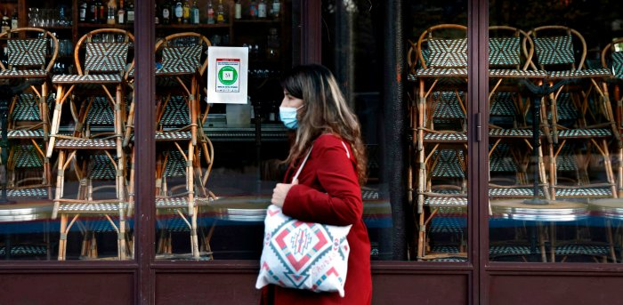 A woman walks past a closed restaurant in Paris on November 18, 2020, amid a second lockdown in France aimed at containing the spread of Covid-19 pandemic caused by the novel coronavirus. Credit: AFP