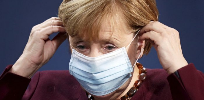 German Chancellor Angela Merkel puts on her face mask after holding a joint news conference with Finance Minister Olaf Scholz after a virtual G20 summit meeting. Credit: AP/PTI.