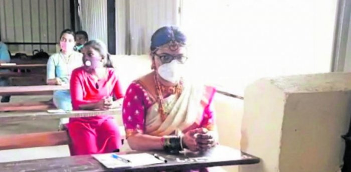 Swathi, the bride, takes the competitive examination at the examination centre in Junior College, Madikeri, on Sunday.