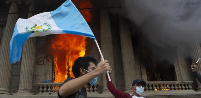 A protester waves a national flag as the Congress building burns in the background, set on fire by protesters, in Guatemala City, Saturday, Nov. 21, 2020. Credit: AP Photo