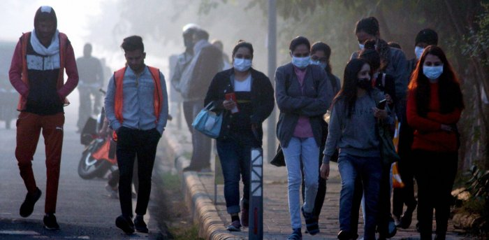 Commuters wearing warm clothes walk on a street on a cold winter morning, in Gurugram. Credit: PTI Photo