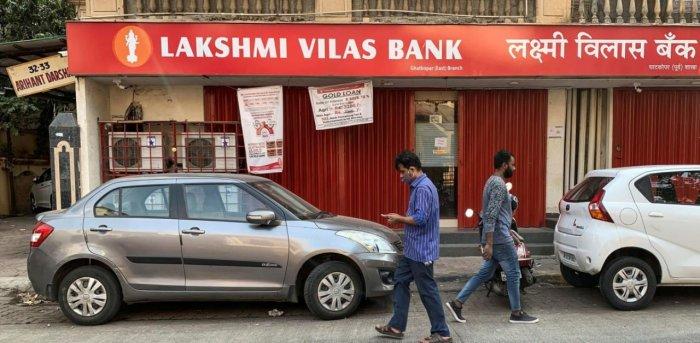 People walk past a Lakshmi Vilas Bank branch in Mumbai. Credit: Reuters.