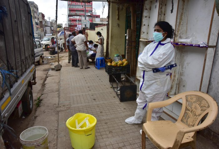 A healthcare worker waits for people to test them for Covid-19 on a footpath at Chickpet, Bengaluru's traditional business hub. DH PHOTO/IRSHAD MAHAMMAD