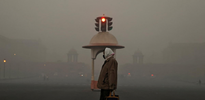 An office-goer walks past a traffic signal near various government ministries on a smoggy morning in New Delhi. Credit: Reuters Photo