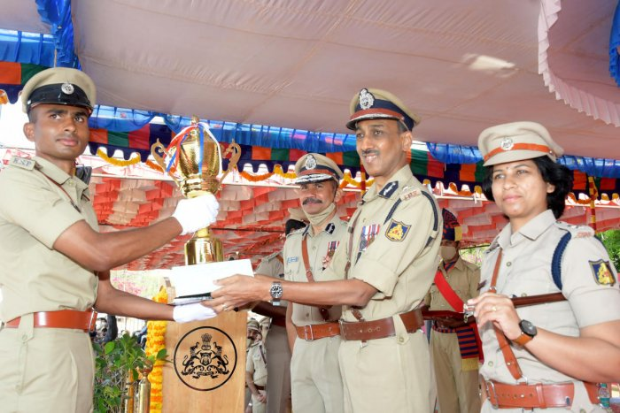 Director General of Police, Training, Padam Kumar Garg gives away Chief Minister Trophy to probationary Police Sub-Inspector K R Chintan, during passing out parade at Parade grounds in Mysuru on Saturday. KPA Director Vipul Kumar and Deputy Director Suman Pennekar are seen. Credit: DH Photo
