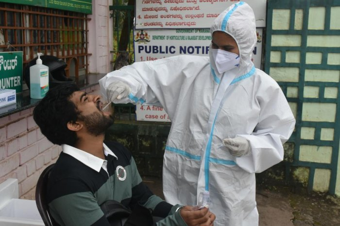 A healthcare worker collects a swab sample from a tourist at Raja Seat in Madikeri.