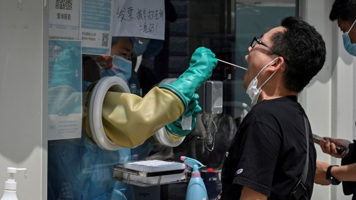A health worker takes a swab sample from a man to be tested for Covid-19 coronavirus at a nucleic acid sample collection station in Beijing. Credit: AFP Photo