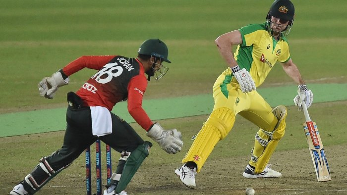 Australia's Ashton Turner (R) plays a shot as Bangladesh's wicketkeeper Nurul Hasan tries to catch the ball during the fourth T20. Credit: AFP Photo
