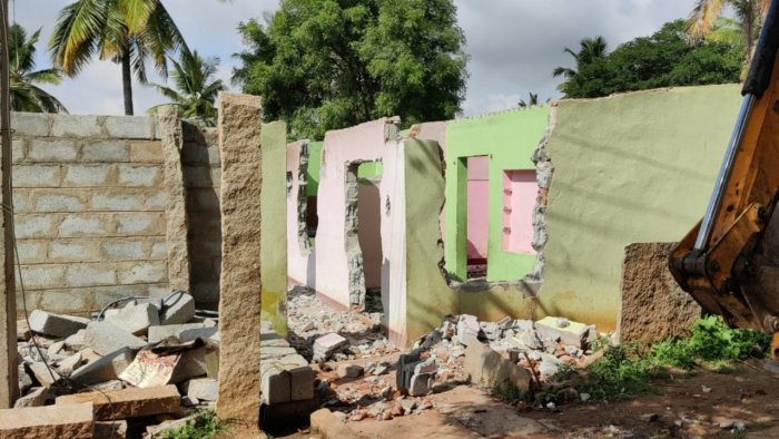 Photo caption: District administration officials bring down a building illegally constructed on government land in Anagalapura village in Bengaluru East taluk. Credit: Special Arrangement