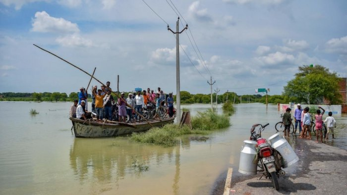People use a boat to cross a waterlogged area after rising water level in river Ganges caused flooding at Badara Sanuti village, near Allahabad on August 6, 2021. Credit: AFP Photo
