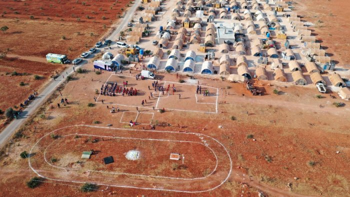 """This aerial view shows a field at a camp for displaced Syrians hosting the so-called """"Camp Olympics 2020"""" in the town of Fuaa, in the northwestern Syrian last major rebel bastion of Idlib, on August 7, 2021, as 120 boys from 12 different camps gather for their own version of the Olympic games, at the end of the Tokyo Olympics. Credit: AFP Photo"""