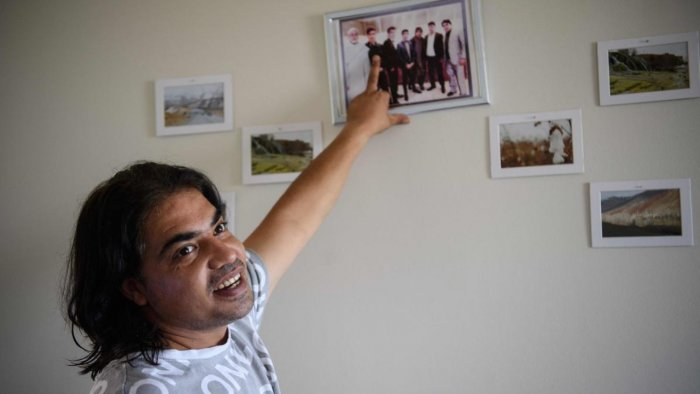 Samim Zalmy shows pictures of himself with his brothers and their father in his apartment in Falls Church, Virginia. Credit: AFP Photo