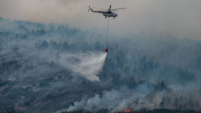 A helicopter drops water on a wildfire on an area near the village of Ikizce, in the Mugla province, on August 6, 2021. - In Turkey, at least eight people have been killed and dozens more hospitalised as the country struggles against its deadliest wildfires in decades. Credit: AFP Photo