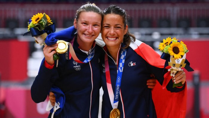 France's goalkeeper Amandine Leynaud (L) and France's goalkeeper Cleopatre Darleux celebrate with their gold medals on the podium after the women's handball event of the Tokyo 2020 Olympic Games at the Yoyogi National Stadium in Tokyo. Credit: AFP photo