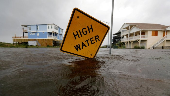 Flood waters lap at a high water warning sign that was partially pushed over by Hurricane Florence on Oak Island, North Carolina. Credit: Reuters File Photo
