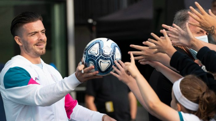 Jack Grealish hands a football to supporters. Credit: AP Photo