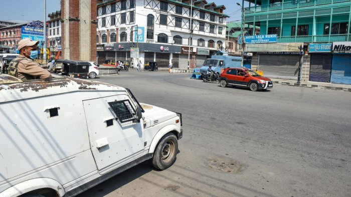 A security personnel stands guard in an armoured vehicle during a strike on the second anniversary of the abrogation of Art 370, in Srinagar. Credit: PTI Photo