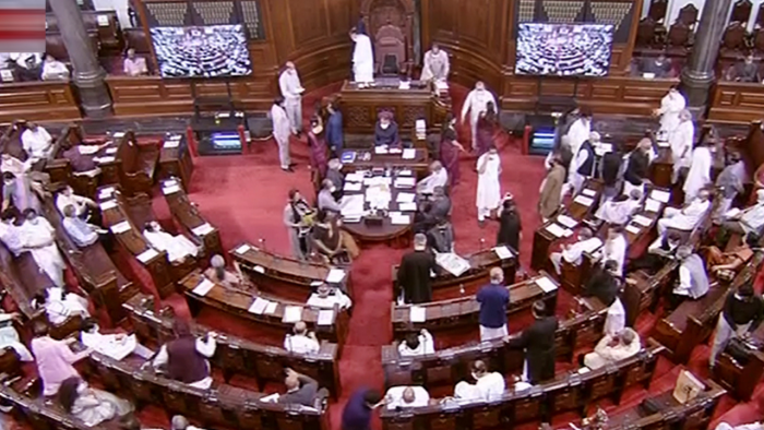 Some Opposition members climbed atop the table occupied by Rajya Sabha officials in the Well. Credit: PTI Photo