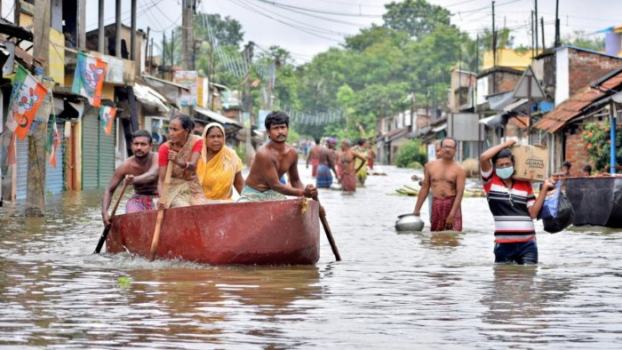 People wade through a flooded street to collect food and drinking water from a distribution centre in Amta town. Credit: Reuters Photo