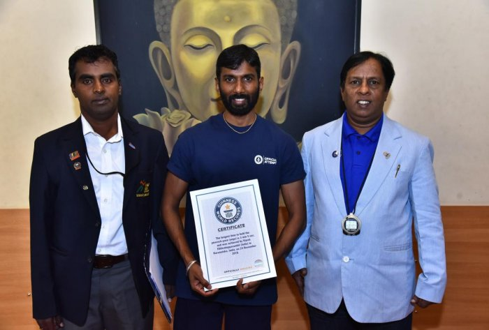 Vijesh Elikattepparambil (centre) recently entered the Guinness Book of World Records for holding the scorpion pose for two minutes and 14 seconds.