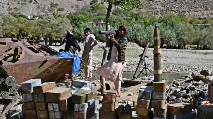 Taliban fighters stand next to ammunition along a road in Malaspa area, Bazark district, Panjshir. Credit: AFP Photo