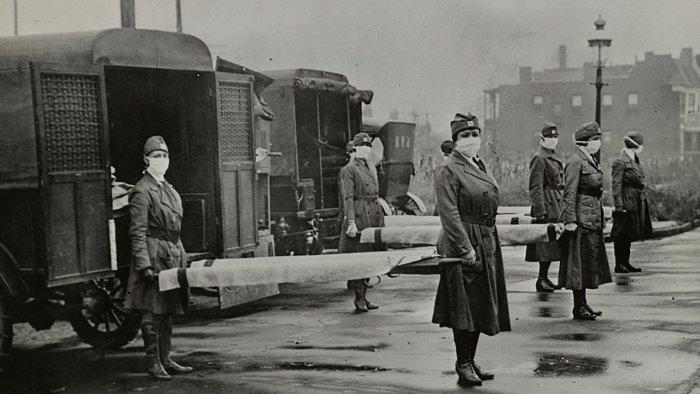 Mask-wearing women hold stretchers near ambulances during the Spanish Flu. Credit: Reuters File Photo