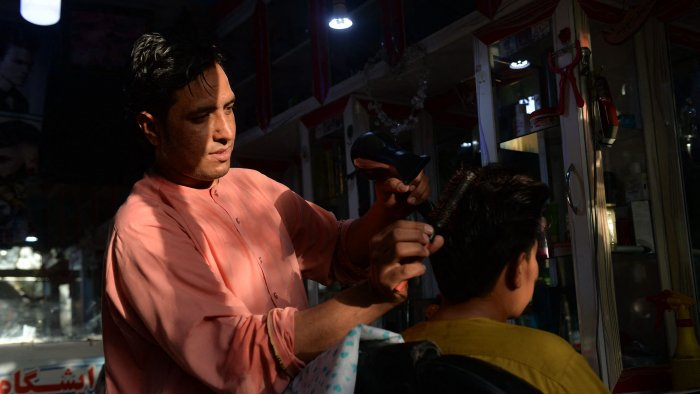 24-year-old Nader Shah (L) attends a customer at his barbershop in Herat. Credit: AFP Photo