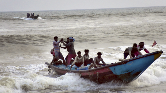 Fishermen shift their boats apprehending low-pressure rain at Pentokota fishing village in Puri. Credit: PTI Photo