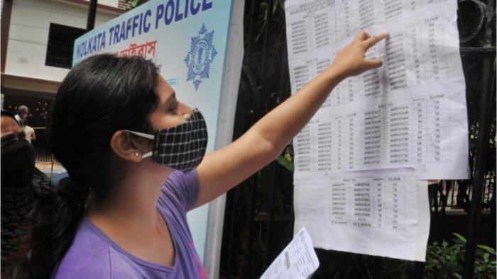 An aspirant looks for her seat number before appearing in National Eligibility cum Entrance Test-2021 (NEET) at an examination centre in Kolkata. Credit: PTI File Photo