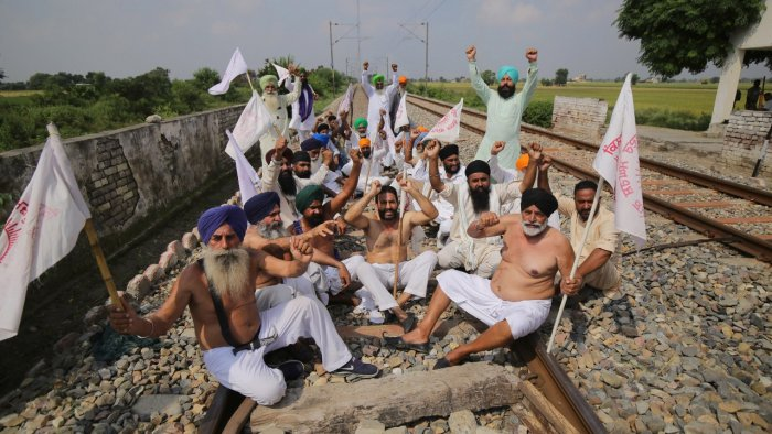 Farmers block the railway tracks during their 'Bharat Bandh' against central government's three farm reform laws, at Devi Dass Pura on the outskirts of Amritsar. Credit: PTI Photo