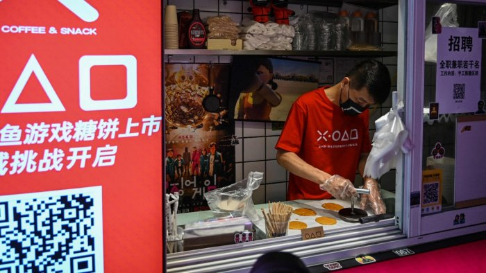 A man in a shop making dalgona candy, featured in Squid Game, in Shanghai. Credit: AFP Photo