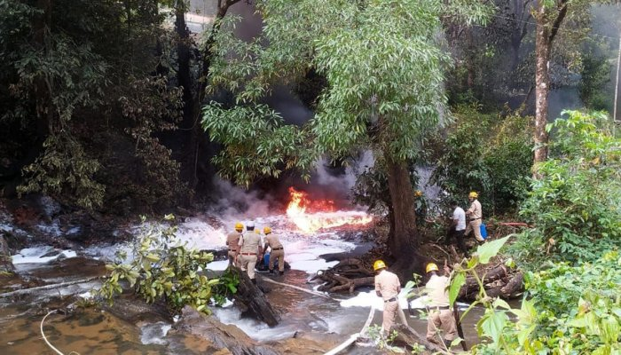 Firemen try to douse the blaze in a stream following a tanker accident at Aarathibail Ghat on NH-63 near Yellapur in Uttara Kannada district on Wednesday. Credit: DH Photo