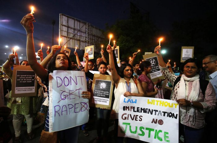 People hold candles and placards during a protest against the rape of an eight-year-old girl, in Kathua, near Jammu, a teenager in Unnao, Uttar Pradesh, and an eleven-year-old girl in Surat, Gujarat, in Ahmedabad. Reuters photo