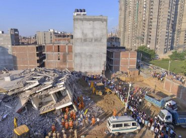 NDRF and local authorities carry out rescue work at the site of a collapsed building at Shahberi village, in Greater Noida West on Wednesday, July 18, 2018. A six-storey under-construction building collapsed in Greater Noida, killing at least two persons and trapping several others under the debris. (PTI Photo)