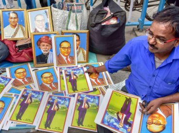 A man sells photos of Dr Bhimrao Ramji Ambedkar at a rally organised on the occasion of his death anniversary, in Kolkata. (PTI Photo)