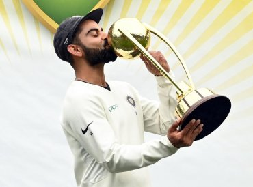 Virat Kohli kisses the Border-Gavaskar trophy as the Indian team celebrates their series win on the fifth day of the fourth and final cricket Test against Australia at the Sydney Cricket Ground in Sydney on January 7, 2019. (AFP)