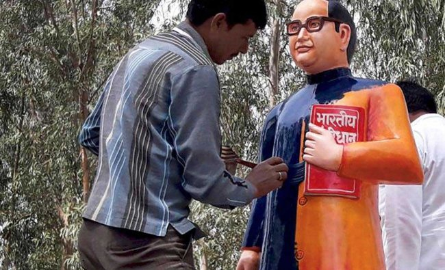 A BSP worker paints the newly constructed statue of BR Ambedkar in blue in Badaun on Tuesday. The saffron-statue raised controversy as Ambedkar\'s statues have always been shown in blue coat. PTI Photo