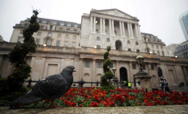 A pigeon stands in front of the Bank of England in London, Britain