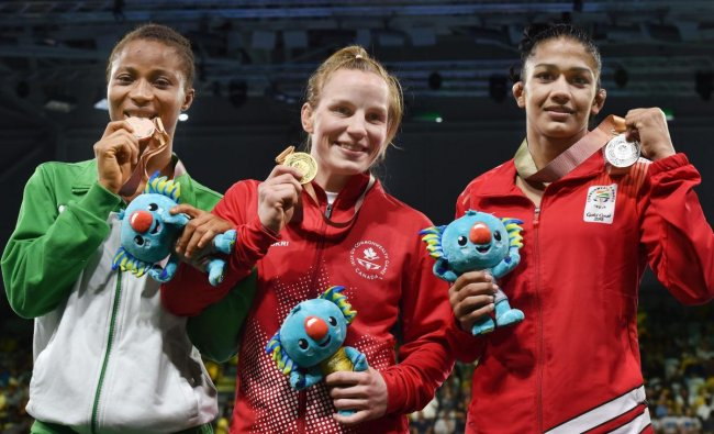 Gold medalist Canada\'s Diana Weicker, silver medalist India\'s Babita Kumari and bronze medalist Nigeria\'s Bose Samuel during the medal ceremony of the women\'s freestyle 53 kg Nordic category at the Commonwealth Games 2018 in Gold Coast, on Thursday. (PTI Photo)