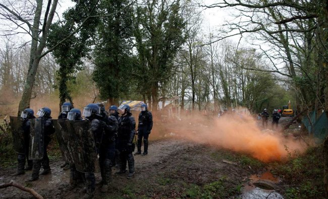 French gendarmes secure a road during clashes with protesters during an evacuation operation in the zoned ZAD (Deferred Development Zone) in Notre-Dame-des-Landes, near Nantes, France