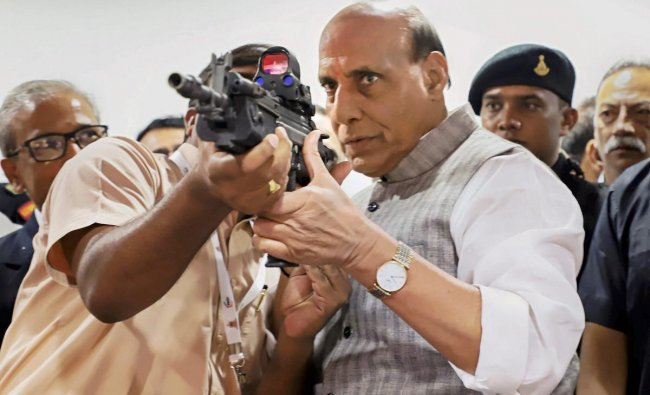 Rajnath Singh checks out a gun during the inauguration of the 2nd Conference of Young Superintendents of Police, organized by the Director General of Bureau of Police Research & Development (BPR&D), in New Delhi. (PTI Photo)