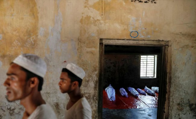 Bodies of Rohingya refugees, who died when their boat capsized while fleeing Myanmar, are placed in a local madrasa in Shah Porir Dwip, in Teknaf, near Cox\'s Bazar in Bangladesh, October 9, 2017. REUTERS/Damir Sagolj