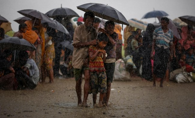 Rohingya refugees try to take shelter from torrential rain as they are held by the Border Guard Bangladesh (BGB) after illegally crossing the border, in Teknaf, Bangladesh, August 31, 2017. REUTERS/Mohammad Ponir Hossain