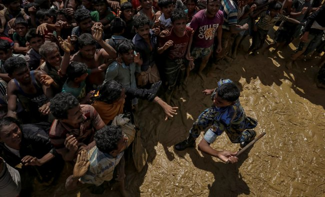 A security officer attempts to control Rohingya refugees waiting to receive aid in Cox\'s Bazar, Bangladesh, September 21, 2017. REUTERS/Cathal McNaughton
